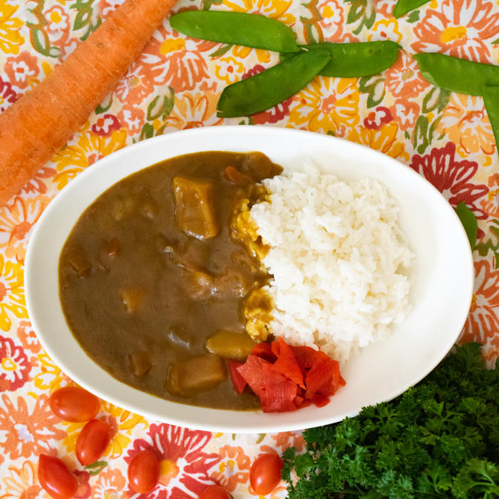 A plate of curry with rice with vegetable pickles