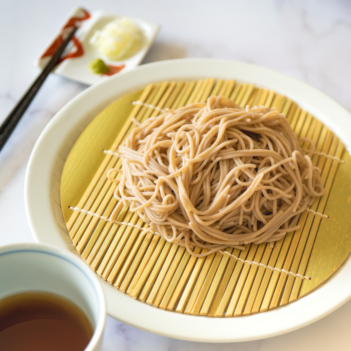 A plate of cold juwari soba noodles next to garnish and a cup of dipping sauce