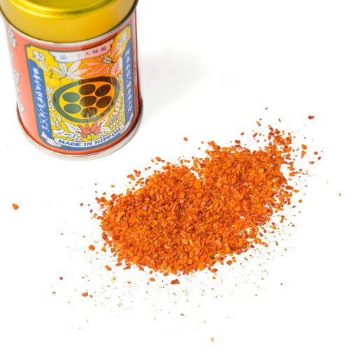 Scattered ichimi pepper next to bottle of the product