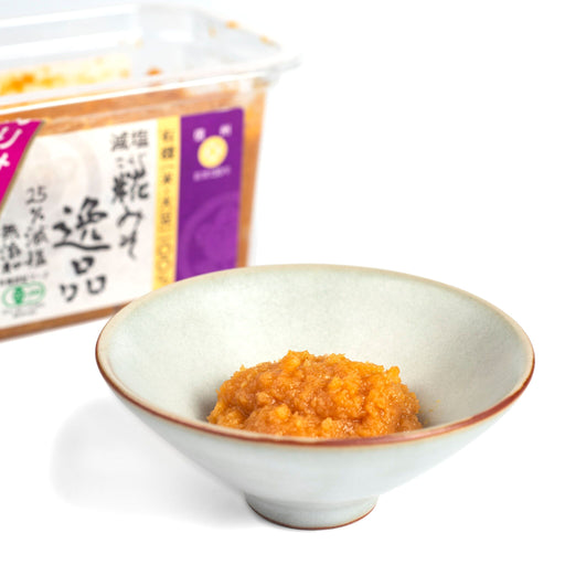 A small bowl of organic koji miso next to box of the product