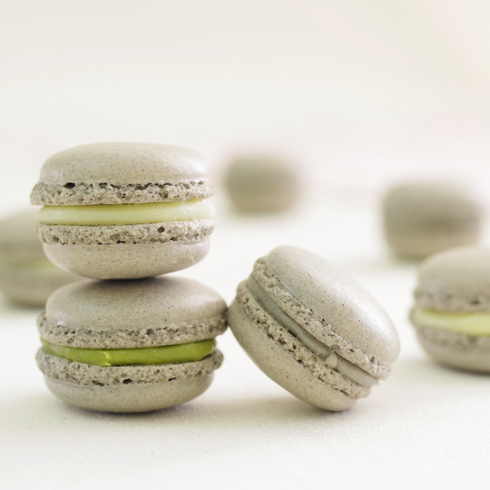 A couple of black sesame macarons stuffed with matcha cream