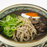 A bowl of soba noodles, scallions, braised meat and boiled egg in black sesame soup