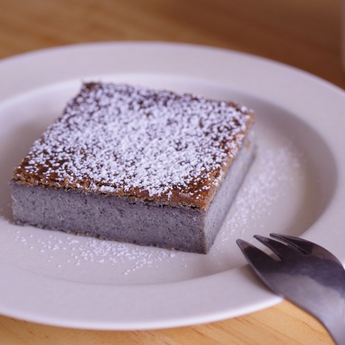 A plate of a slice of black sesame cake topped with powdered sugar