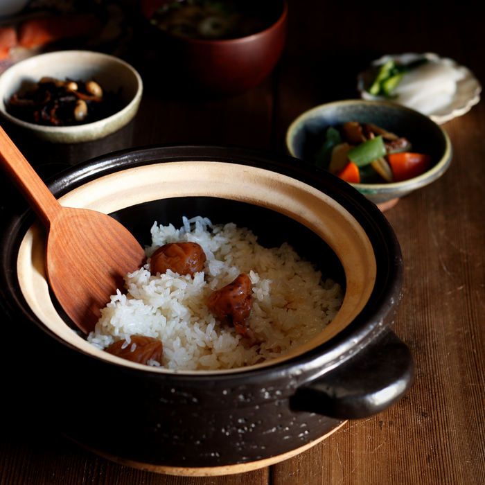 A ceramic pot filled with steamed white rice with three pieces organic umeboshi