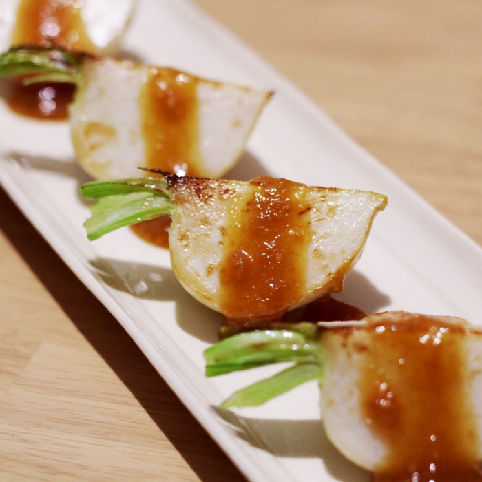 A plate of grilled radish sliced into four pieces and topped with organic yuzu spread