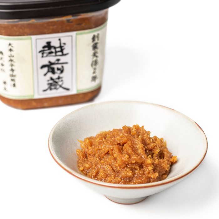 A bowl of miso paste next to a box of the product