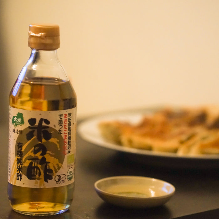 A bottle of the product and a small bowl of the organic rice vinegar in front of a plate of gyoza dumplings