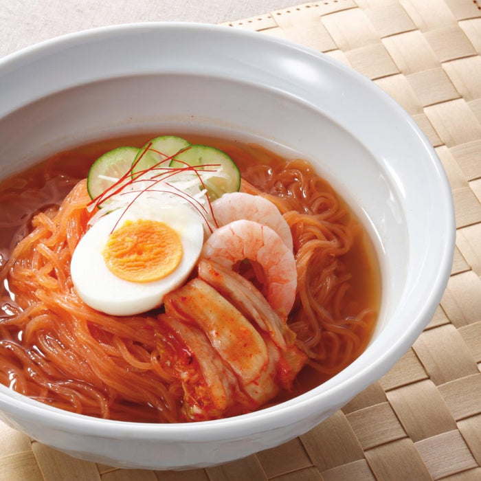 A bowl of carrot blended shirataki noodles soup topped with boiled eggs and shrimps