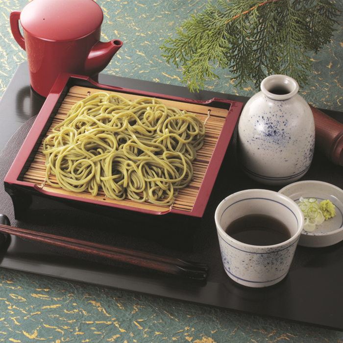 Cha soba noodles on a plate next to a cup of soup and some garnish