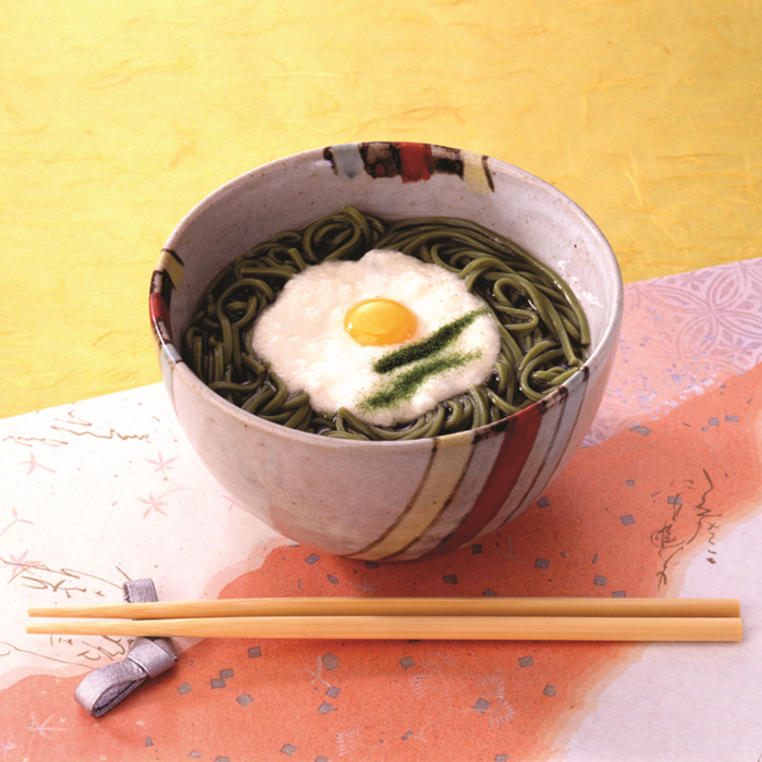 A bowl of cha soba noodles soup topped with egg