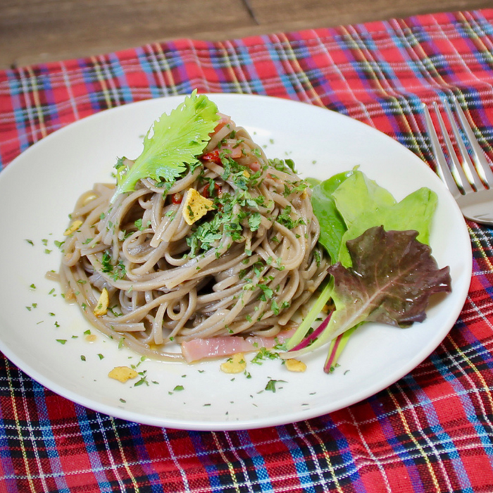 A plate of cold juwari soba noodles topped with garnish