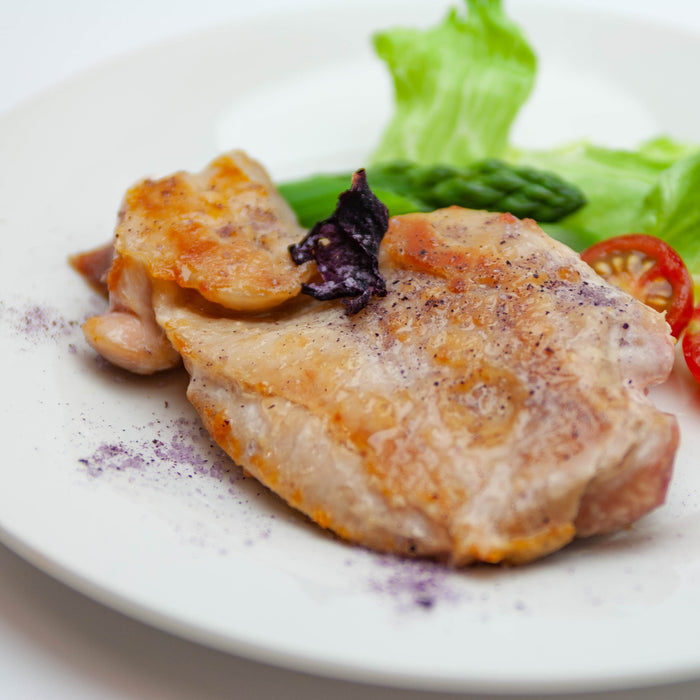 A plate of grilled chicken with rose salt