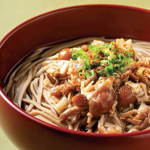A bowl of soba noodles topped with shichimi togarashi pepper powder and mushrooms