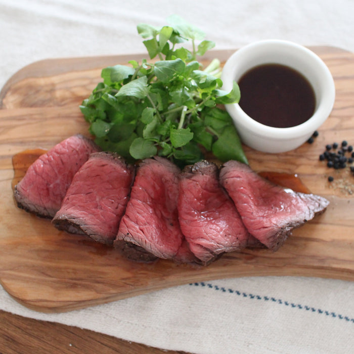 Five slices of roast beef topped with truffle infused soy sauce on wooden board