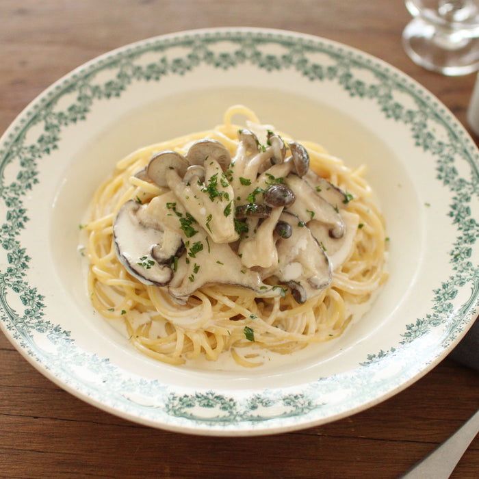A plate of creamy sauce spaghetti topped with mushrooms and truffle infused soy sauce