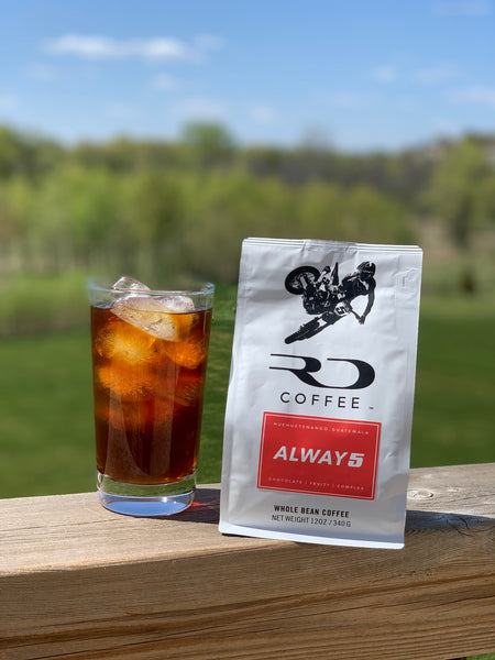 """A cup of cold brew coffee next to a RD Coffee bag of """"ALWAY5"""""""