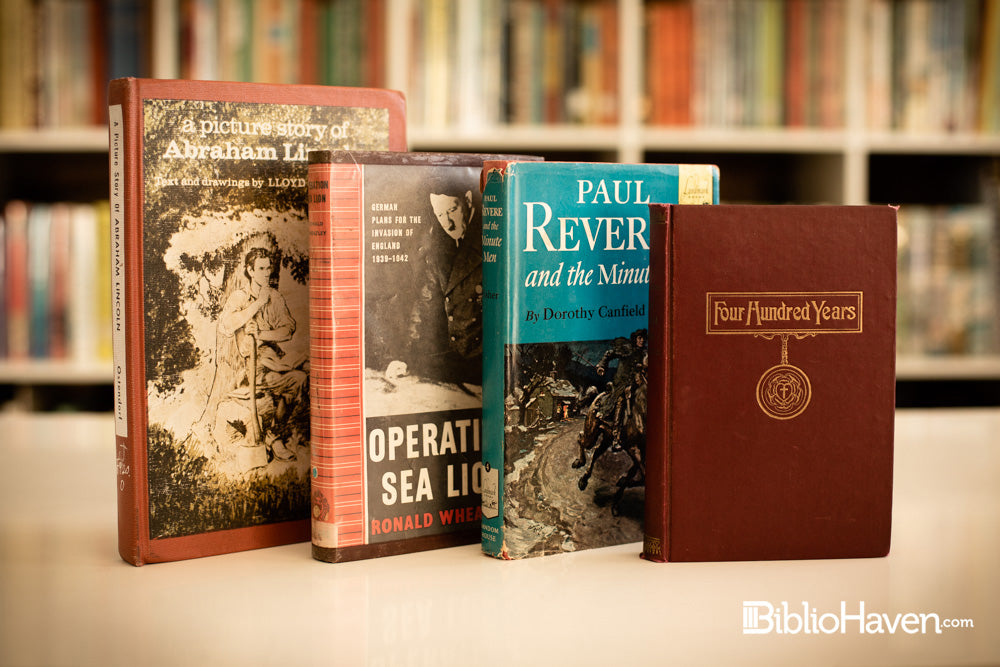 Four history and biography books shown in front of hundreds of books on a shelf blurred in the background.
