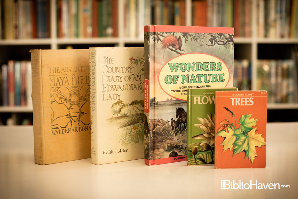 Five nature and animal books shown in front of hundreds of books on a shelf blurred in the background.