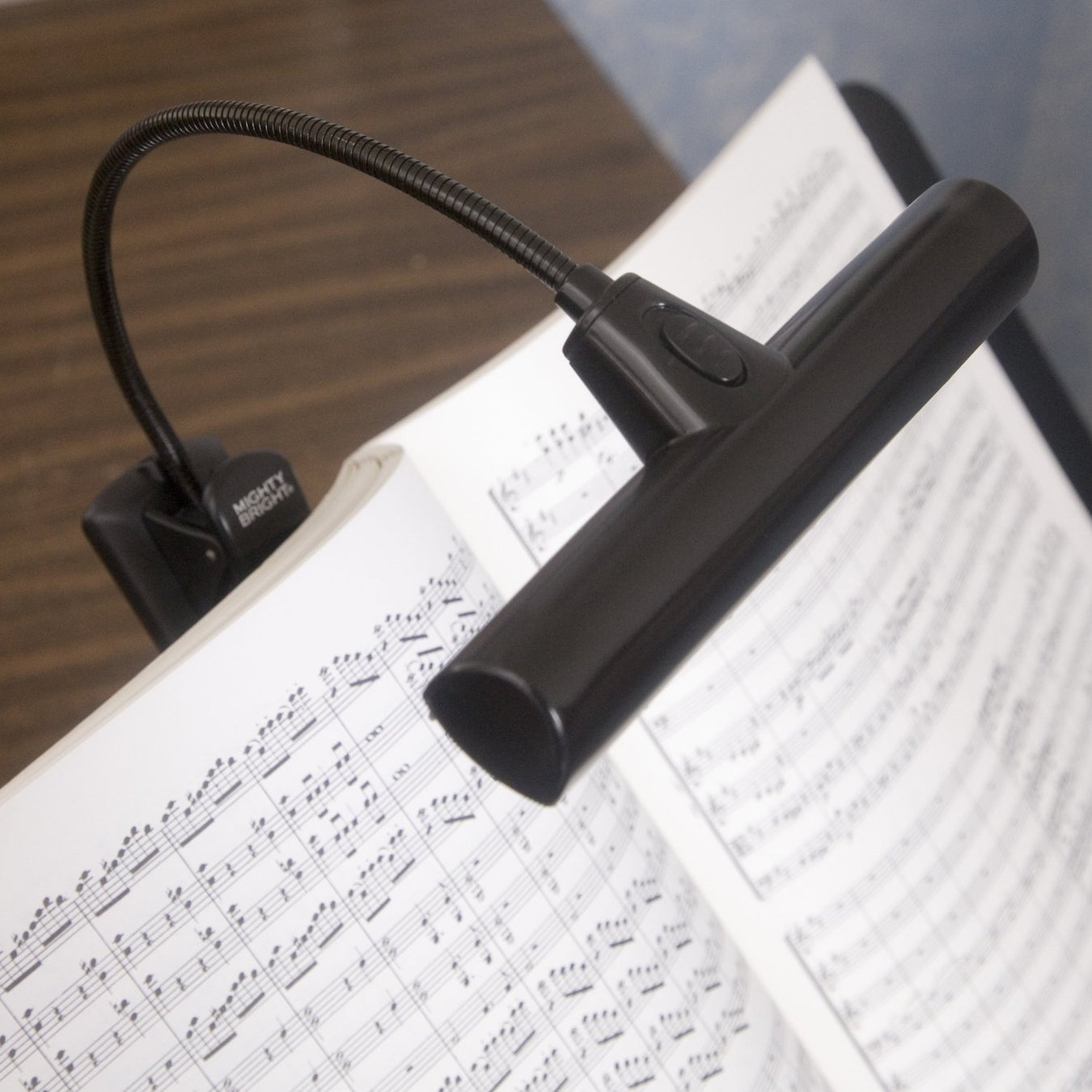 Battery Powered Music Orchestra Light in Black Clipped To A Music Book Illuminating The Pages