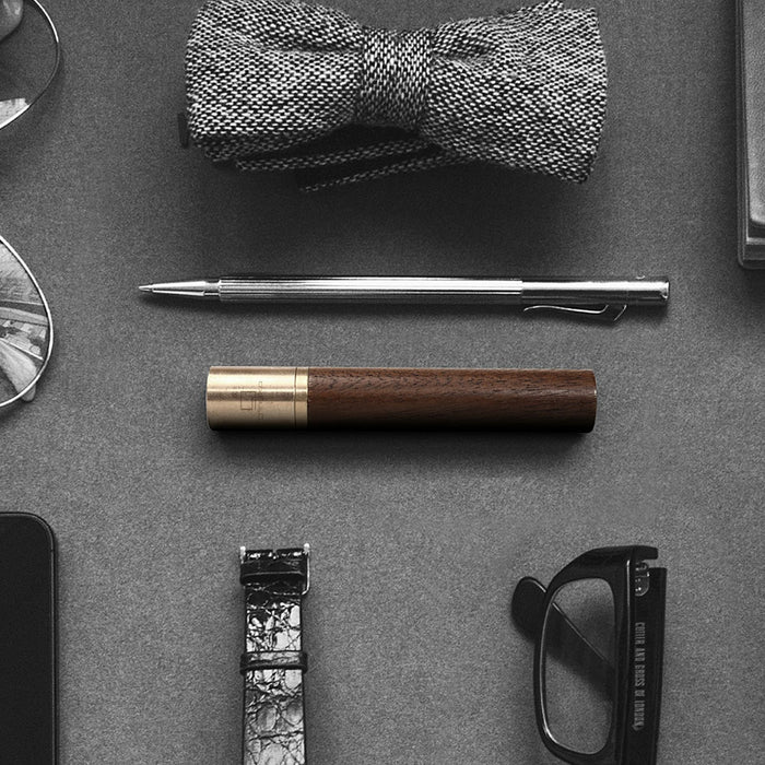 gingko natural wood flameless lighter in american walnut, pictured next to a variety of accessories