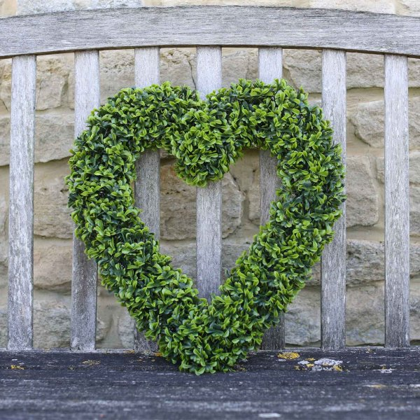 Shop now topiary heart shaped wreath against an outdoor wooden bench