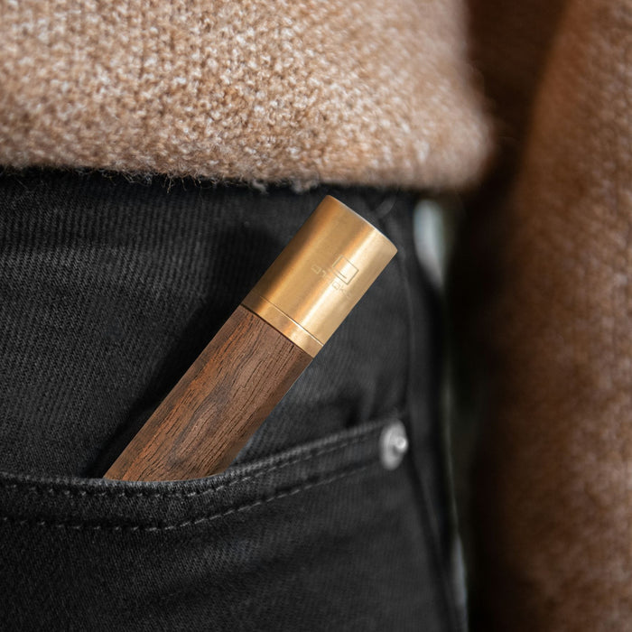 gingko natural wood flameless lighter in american walnut placed in the pocket of a pair of black jeans