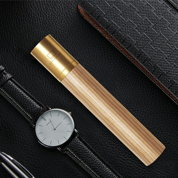 gingko natural wood flameless lighter in white ash placed next to a watch with a black leather strap