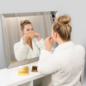girl applying gold lip gel in mirror from care market