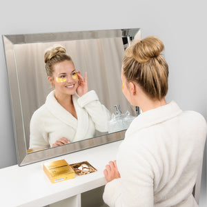 girl looking in mirror wearing under eye mask from care market