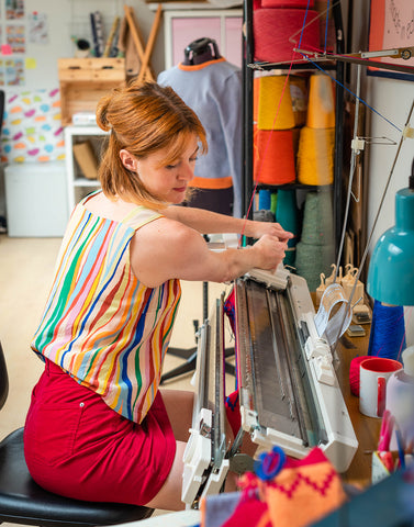 Kathleen sits working at her knitting machine, with lots of bright yarn behind her.