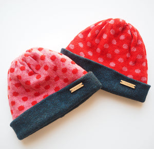 K.Moods Reversible Beanies: two bright beanies, one pink with red polka-dot pattern, and one red with pink polka-dot pattern. Both have a navy band.