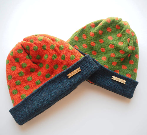 K.Moods Reversible Beanies: two bright beanies, one orange with green polka-dot pattern, and one green with orange polka-dot pattern. Both have a navy band.