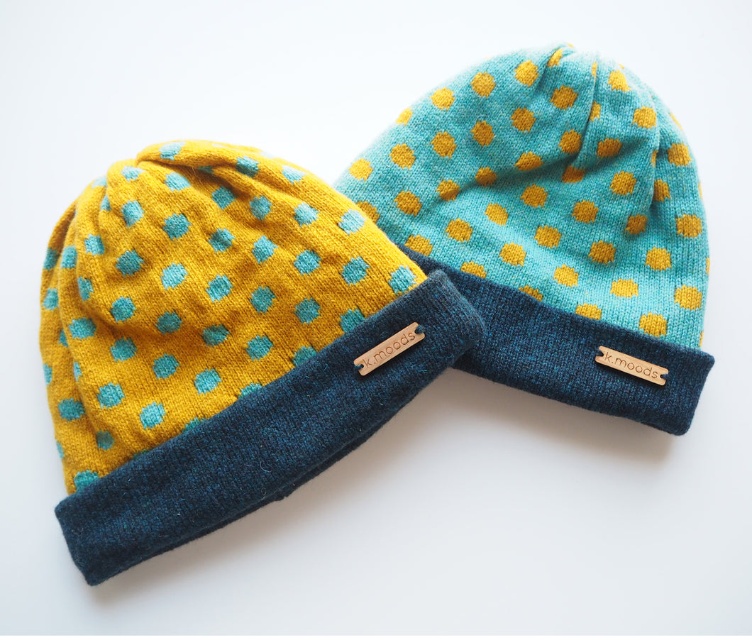 K.Moods Reversible Beanies: two bright beanies, one yellow with blue polka-dot pattern, and one blue with yellow polka-dot pattern. Both have a navy band.