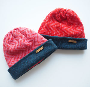 K.Moods Reversible Beanies: two bright beanies, one pink with red zig-zag pattern, and one red with pink zig-zag pattern. Both have a navy band.