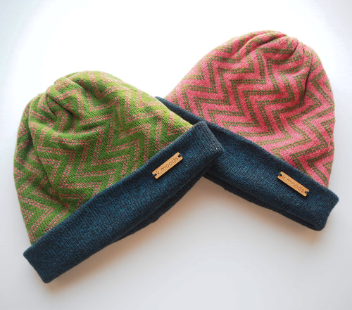 K.Moods Reversible Beanies: two bright beanies, one green with pink zig-zag pattern, and one pink with green zig-zag pattern. Both have a navy band.
