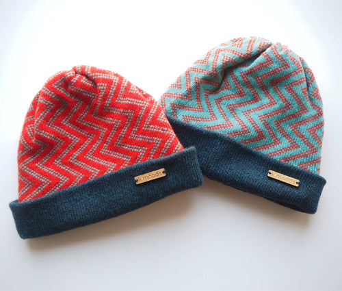 K.Moods Reversible Beanies: two bright beanies, one red with blue zig-zag pattern, and one blue with red zig-zag pattern. Both have a navy band.