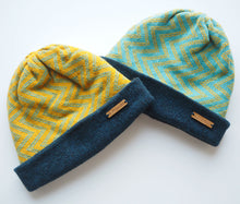 Load image into Gallery viewer, K.Moods Reversible Beanies: two bright beanies, one yellow with blue zig-zag pattern, and one blue with yellow zig-zag pattern. Both have a navy band.