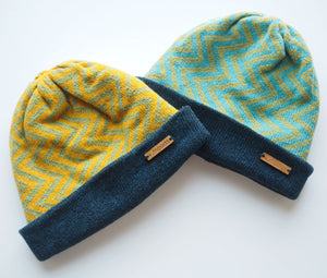 K.Moods Reversible Beanies: two bright beanies, one yellow with blue zig-zag pattern, and one blue with yellow zig-zag pattern. Both have a navy band.