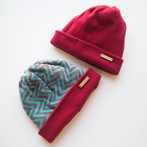 K.Moods Reversible Beanies: two beanies, one bright blue with maroon zig-zag pattern and a maroon band, and one plain maroon beanie.
