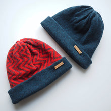 Load image into Gallery viewer, K.Moods Reversible Beanies: two beanies, one bright red with navy zig-zag pattern and a navy band, and one plain navy beanie.