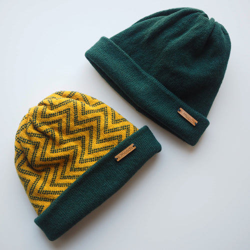 K.Moods Reversible Beanies: two beanies, one bright yellow with green zig-zag pattern and a green band, and one plain green beanie.