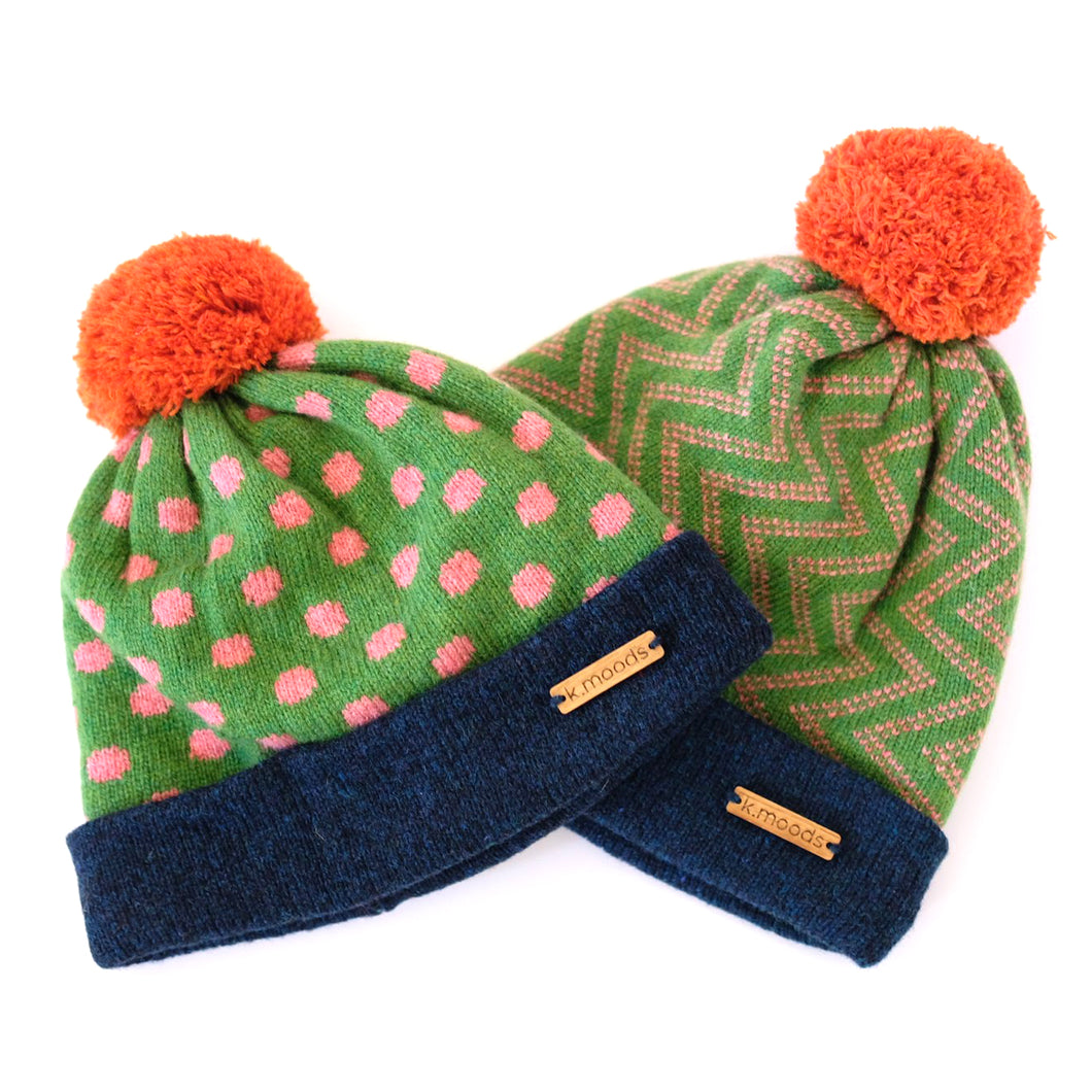 K.Moods Pom-Pom Beanies: two bright green beanies, one with pink polka-dot pattern, and one with pink zig-zag pattern. Both have a navy band, and an orange pom-pom.