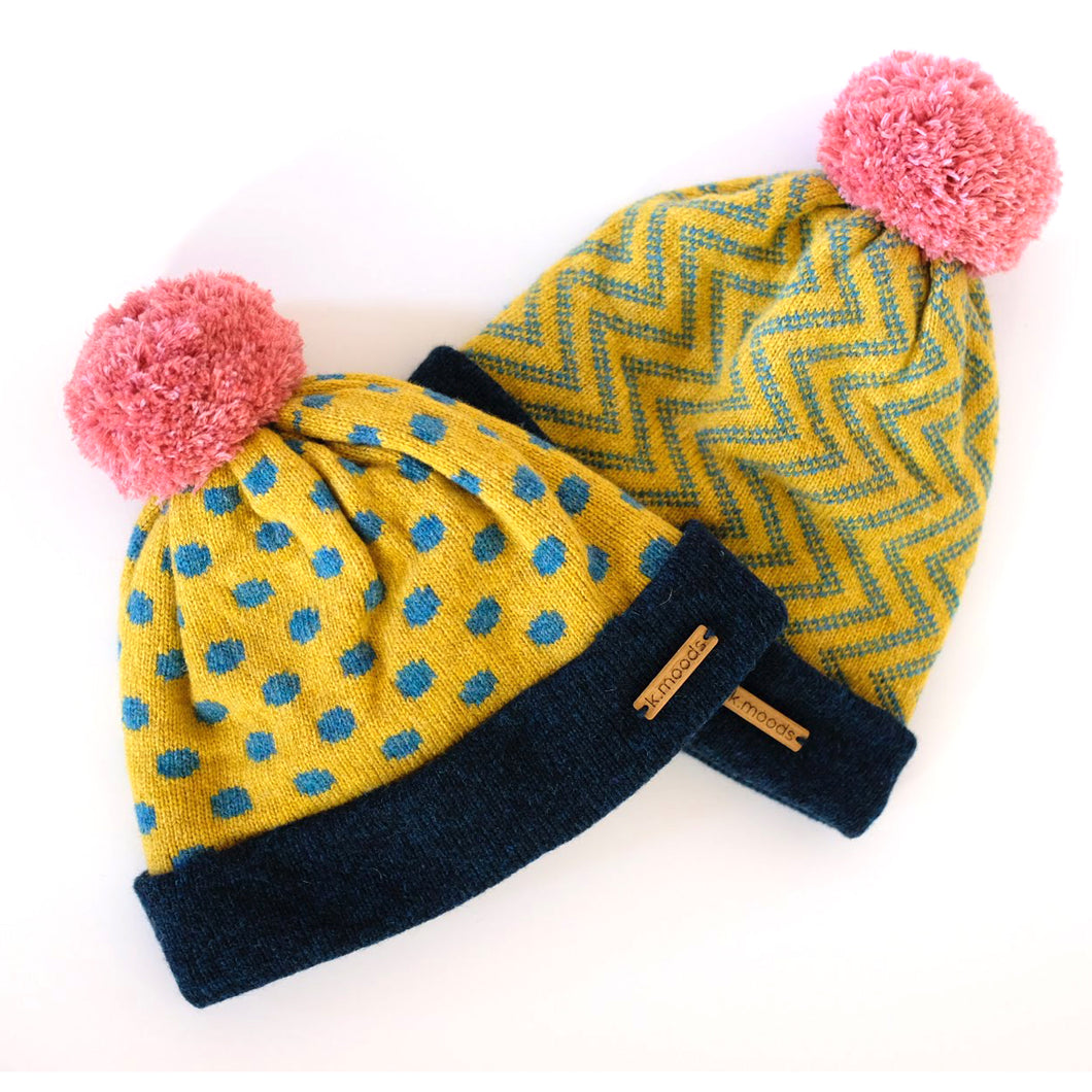 K.Moods Pom-Pom Beanies: two bright yellow beanies, one with blue polka-dot pattern, and one with blue zig-zag pattern. Both have a navy band, and a pink pom-pom.