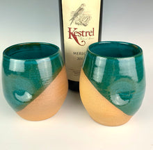 Load image into Gallery viewer, Stemless wine glasses. set of two wheel thrown pottery with finger divots for grip. Jade green glaze over red stoneware clay, glazed at an angle to reveal the clay. shown with wine