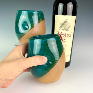 Stemless wine glasses. wheel thrown pottery with finger divots for grip. Jade green glaze over red stoneware clay, glazed at an angle to reveal the clay. shown held by the artist with wine.