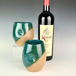 Stemless wine glasses. wheel thrown pottery with finger divots for grip. Jade green glaze over red stoneware clay, glazed at an angle to reveal the clay. shown with wine.