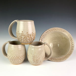 "Carved mugs pictured with a carved rim serving bowl. the pots are thrown on the potters wheel in a red brown clay, then glazed in white. bowl is approximately 7"" in diameter"