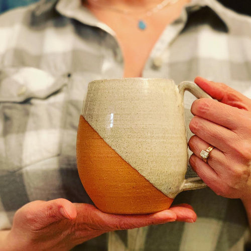 Fern Street Pottery artist, Meredith Chernick holds an Angle-dipped mug. The mug is thrown from red clay and is dipped in speckled white glaze, showing the texture of the clay through. The handle is a full grip, 4 finger handle (for most).