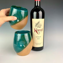 Load image into Gallery viewer, Stemless wine glasses. set of two wheel thrown pottery with finger divots for grip. Jade green glaze over red stoneware clay, glazed at an angle to reveal the clay. shown held by the artist. shown with wine