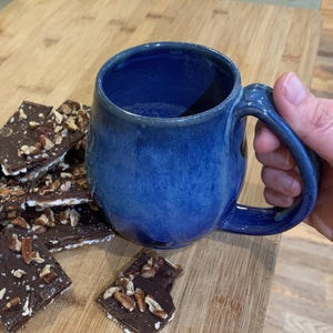 Blue world mug, northwest style coffee mug thrown pottery, with large pulled handle. shown with matzah roca cookies